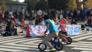 子ども自転車でハイタッチする